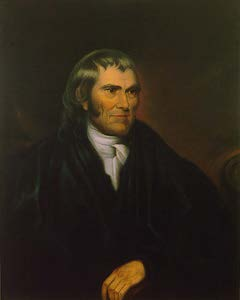 white man with long hair in black judicial robe and white collar. hand crossing chest.
