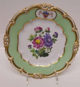 Plate Ornate gilded rim, green and white bands, floral interior. Presidential seal.