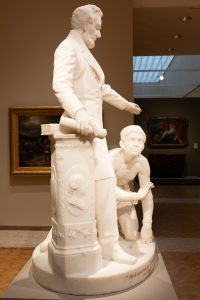 White marble statue group; side view of Abraham Lincoln; hand over kneeling child; rolled up document in other hand