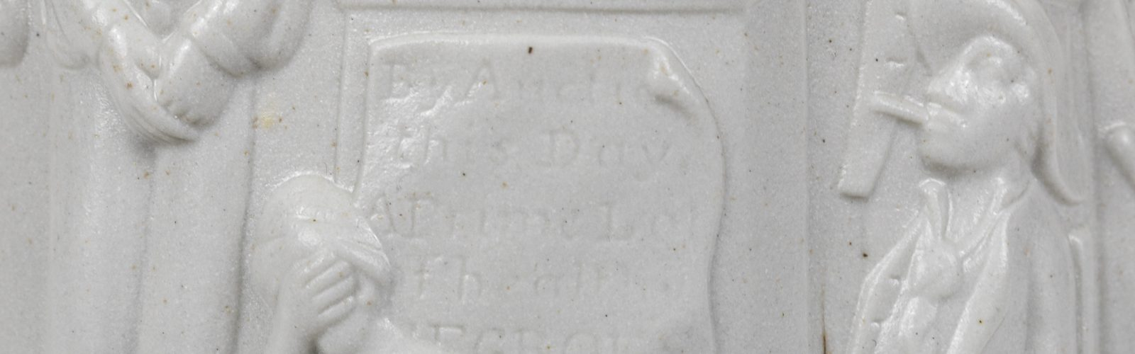 Detal of Slavery jug; part of man on left and right. Panel with illegible letters