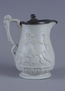 White jug with grey handle; molded scene of man with whip chasing woman and baby across ice